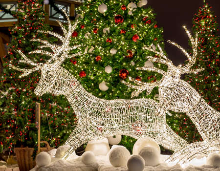Deer made from garland under the decorated Christmas tree at night