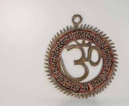 Om sign in circle with mantra made from metal - white background
