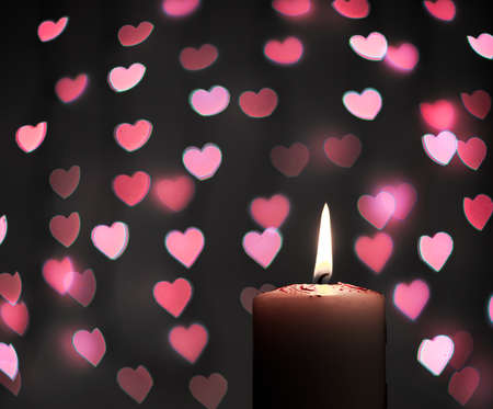 Abstract - burning candle with blur pink heart on black background