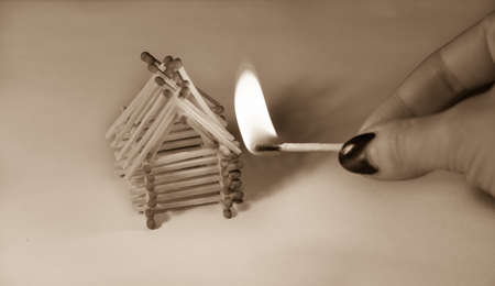 Matches house and hand with burning fire - risk of accident at night sepia