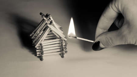 Matches house and hand with burning fire - risk of accident at night Stock Photo