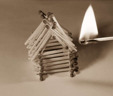 Matches house and match with burning fire - risk of accident at night sepia