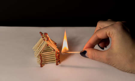 Matches house and hand with burning fire - risk of accident