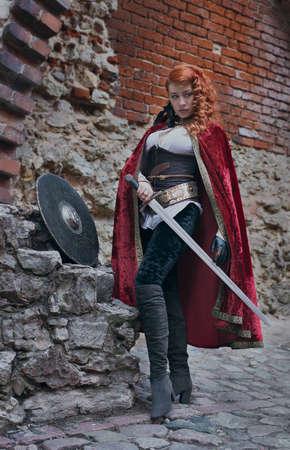 Krieger Frau mit Schwert in der mittelalterlichen Kleidung auf der Straße ist sehr gefährlich Standard-Bild