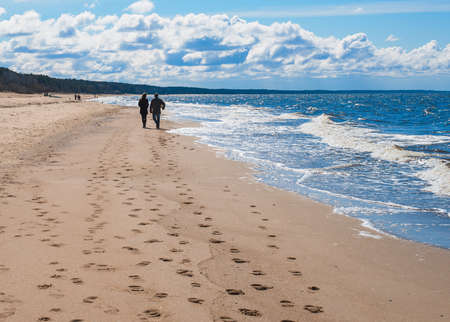 Couple is walking along the beach under blue sky Stock Photo