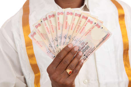 debt management: Hand with Indian thousand rupee notes.