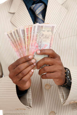 rupee: Hand with Indian thousand rupee notes.