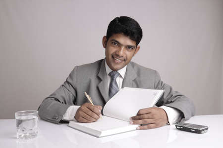Indian business man posing with notebook. photo