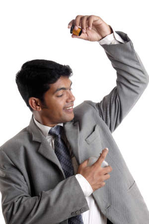 Indian young businessman posing with perfume on white  photo