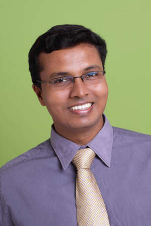 Portrait of indian young businessman on green background.  photo