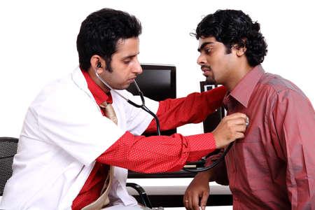 indianin: Indian mÅ'ody lekarz zbadaniu pacjenta Zdjęcie Seryjne