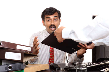 businessman pondering documents: An expressive Indian business man in office  Stock Photo