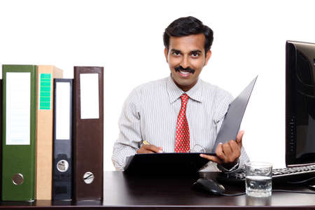Photo of an Indian male happy at work sitting in front of the files  photo