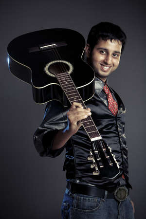 a guitarist boy playing guitar: An Indian guitar player - isolated