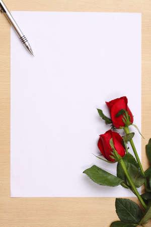 Ball pen & red rose on empty white paper.