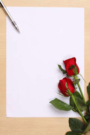 carta de amor: Bol�grafo y rosa roja sobre papel blanco vac�o. Foto de archivo
