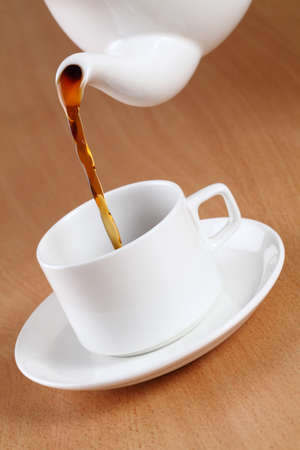 brewing: Teapot pouring tea into a cup. Stock Photo