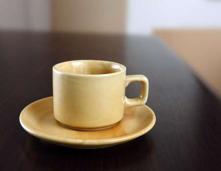yellow tea pot: Tea cup on table