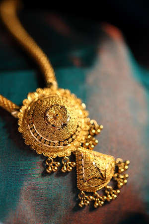 pendant: Gold Necklaces on textured cloth background.  Stock Photo