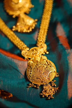 gold necklace: Gold Necklaces on textured cloth background.  Stock Photo