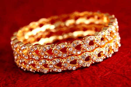 armlet: Gold bracelet on textured background.  Stock Photo
