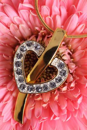 Gold heart pendant on flower background.  photo
