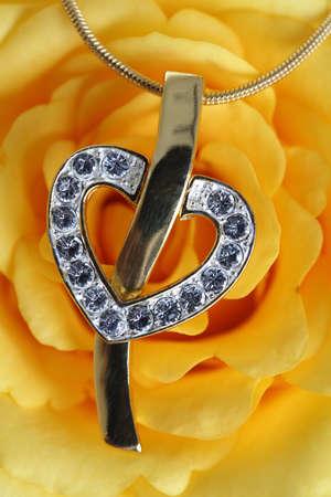 heart diamond: Gold heart pendant on flower background.