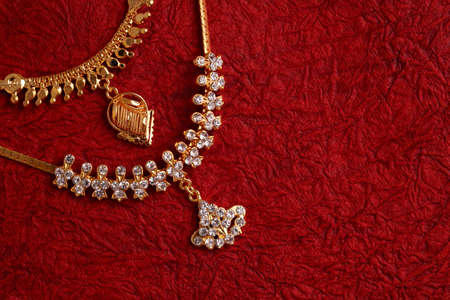 gold jewellery: Gold Necklaces on textured red background.