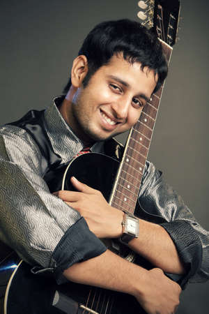 An Indian guitar player - isolated on grey   photo