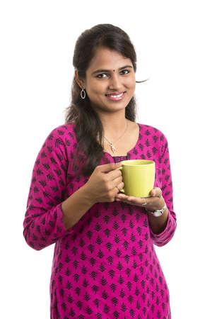 fille indienne: Attractive jeune femme indienne est montrant tasse de thé vert arôme sur fond blanc