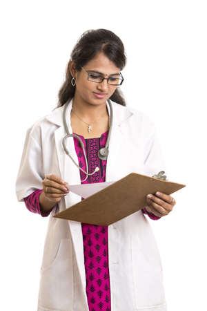 Attractive young Indian Female Doctor with notepad isolated on white   photo