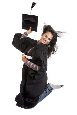 Jumping Indian graduation young woman on white background. photo