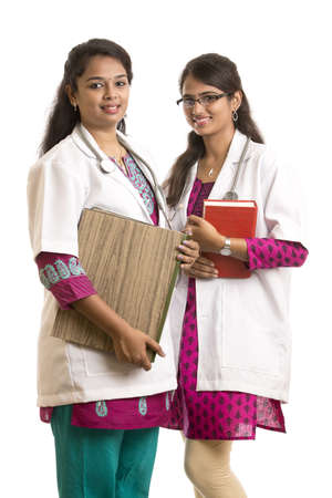 Two young Indian Female Doctors with book isolated on white. photo