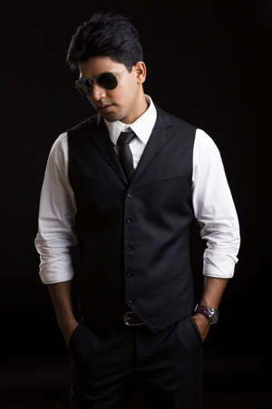 working class: Handsome Indian young businessman posing on black background