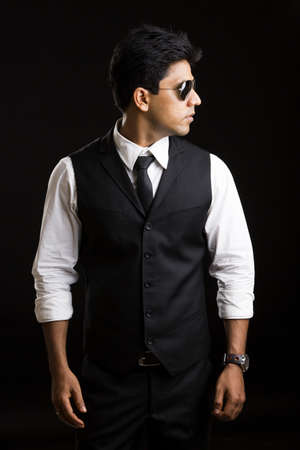 Handsome Indian young businessman posing on black background  photo