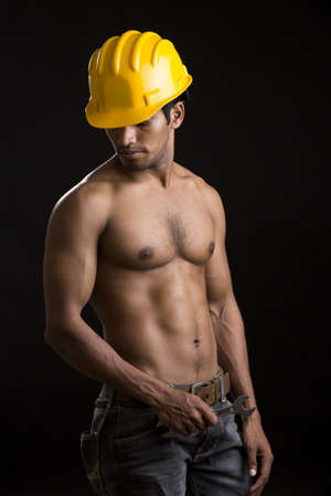 Healthy muscular young man with yellow helmet on black  photo