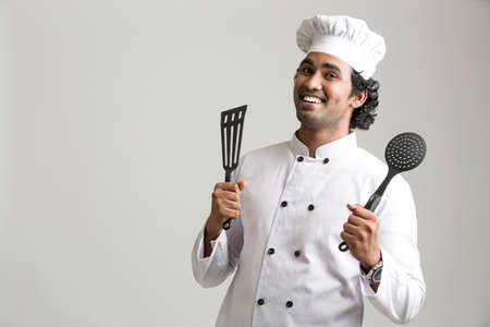 cocinero: Alegre cocinero feliz cocina con utensilios aislados sobre fondo gris
