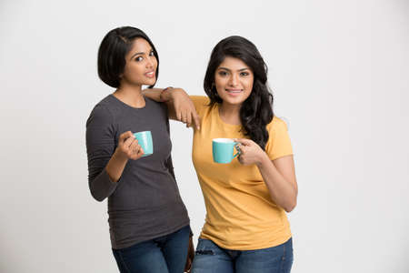 together standing: Two happy young female friends posing with coffee cups on white background.