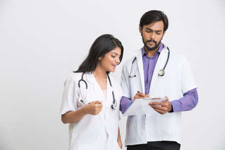 a lady doctor: Examining two young Indian attractive doctors on white background.