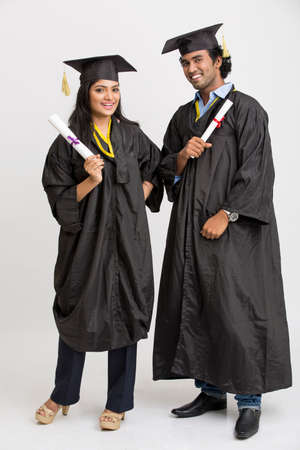 gown: Cheerful Indian college graduates wearing cap and gown holding diploma on white background
