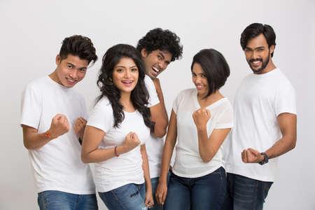 jovenes felices: Feliz grupo de estudiantes indios que muestran la muestra del éxito en el fondo blanco.