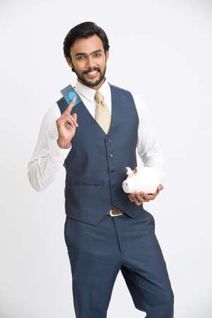 hindu: Successful businessman holding credit card with piggy bank on white background.