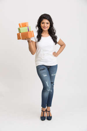 indian sweet: beautiful Indian young woman with gift boxes on white background