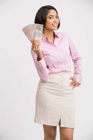 rupee: Smiling young business woman holding rupee notes in her hands