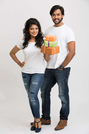 carrying girl: Happy Indian young man and woman carrying gift boxes on white background.