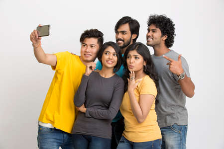 Cheerful group of Indian young friends taking selfie in mobile on a white background.