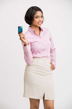 debit: Young pretty smiling Indian girl showing her credit card to the camera.