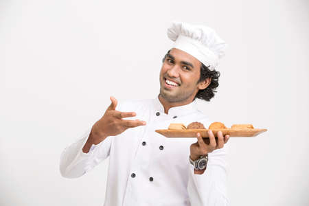 eating food: A male chef with cookies isolated over grey gradient background