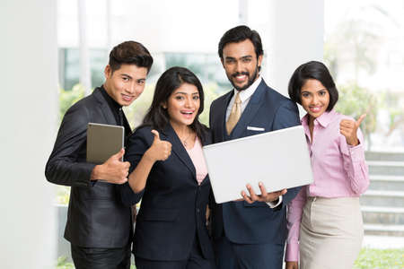 Happy Indian businessman standing with his team at office.