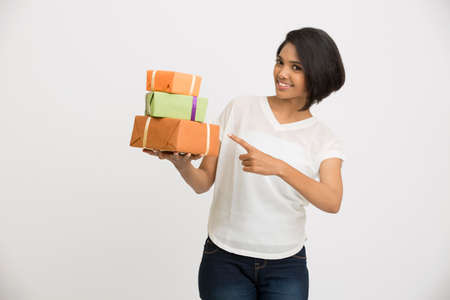 portrait young girl studio: Beautiful Indian young woman poining her gift boxes on white background Stock Photo